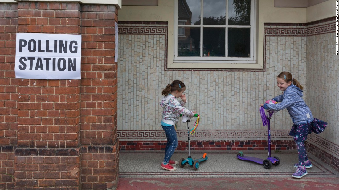 Children play on scooters outside a polling station in London.