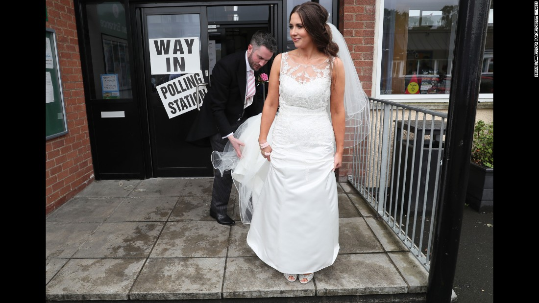 Sorcha Eastwood, an Alliance Party candidate in Northern Ireland, stands outside a polling station in Lisburn after casting her vote. She and her husband, Dale Shirlow, were married earlier in the day.