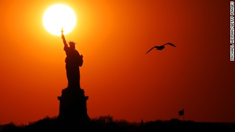 NEW YORK, NEW YORK - JUNE 02: The sun sets behind the Statue of  Liberty as a seagull flies past on June 02, 2017 in New York City. (Photo by Michael Heiman/Getty Images)