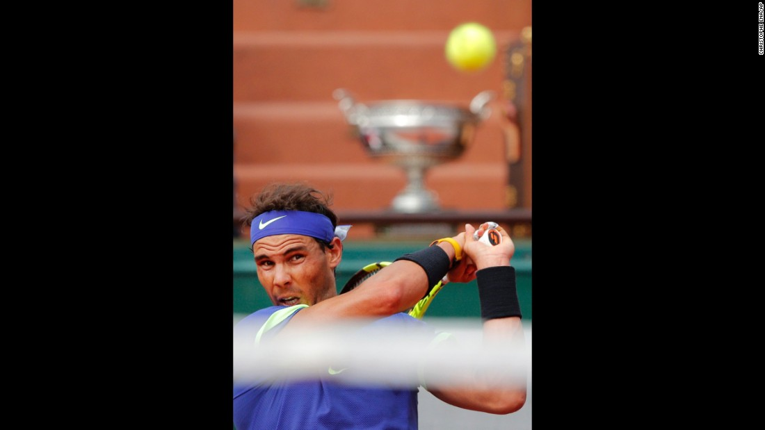 The winner's trophy is seen in the background as Nadal hits a backhand.