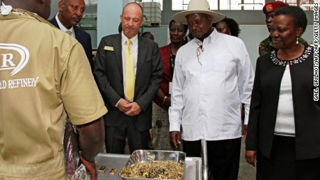 Uganda's President Yoweri Museveni inspects gold flakes at a refinery in Entebbe. The sector has grown rapidly but a new report alleges rampant corruption.