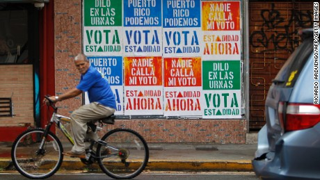 A man rides his bicycle in front of a wall covered with campaign posters promoting Puerto Rico's statehood in San Juan.
