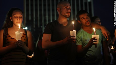 ORLANDO, FL - JUNE 12: Joshua Rivero and Brandon McMillan (C-R) hold candles as they attend a one year anniversary memorial service for victims of the mass shooting at the Pulse gay nightclub behing held at Lake Eola Park on June 12, 2017 in Orlando, Florida.  Omar Mateen killed 49 people at the club a little after 2 a.m. on June 12, 2016.  (Photo by Joe Raedle/Getty Images)