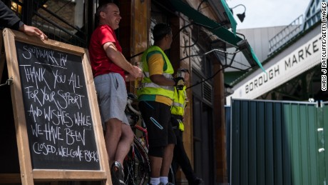 Cyclists drink beer outside the Southwark Tavern which reopened for business on Sunday.