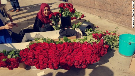 A volunteer poses by red roses given out near the London Bridge on Sunday.