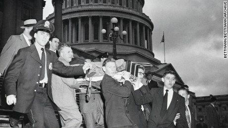 "Rep. Kenneth Roberts shown here being carried down the Capitol steps after Puerto Rican nationalists opened fire in the Capitol Building, shouting ""Free Puerto Rico."""