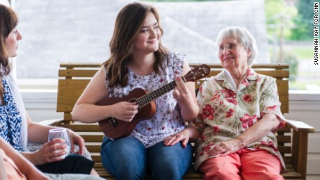 "Emma Pino plays the ukulele next to her grandmother, Helen Romage, on her front porch in Mount Hope, West Virginia. Pino plans to attend West Virginia University in the fall, but says she'll likely leave the state after college. ""I will probably always have family ties here so it will be hard to let all that go, but I think I need to."""