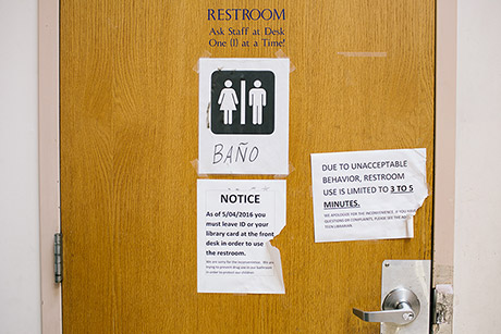 A notice on the bathroom door informs patrons of rules to use the bathroom at McPherson Square Library.