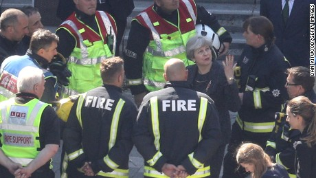 British  Prime Minister Theresa May speaks to firefighters Thursday as she visits Grenfell Tower.