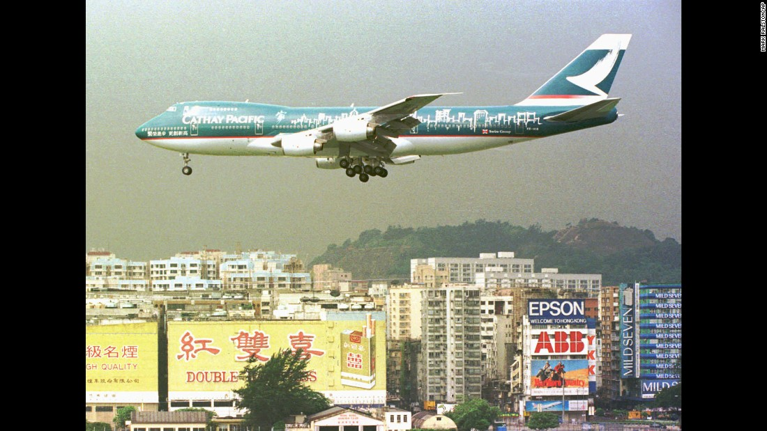 A Cathay Pacific Boeing-747 jet flies over residential buildings near Hong Kong's Kai Tak airport, on June 19, 1997.