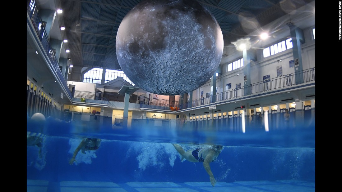 "People in Rennes, France, swim under ""Museum of the Moon,"" an installation by British artist Luke Jerram, at the Saint-Georges public swimming pool on Monday, June 12. The artwork features detailed NASA images of the moon's surface."