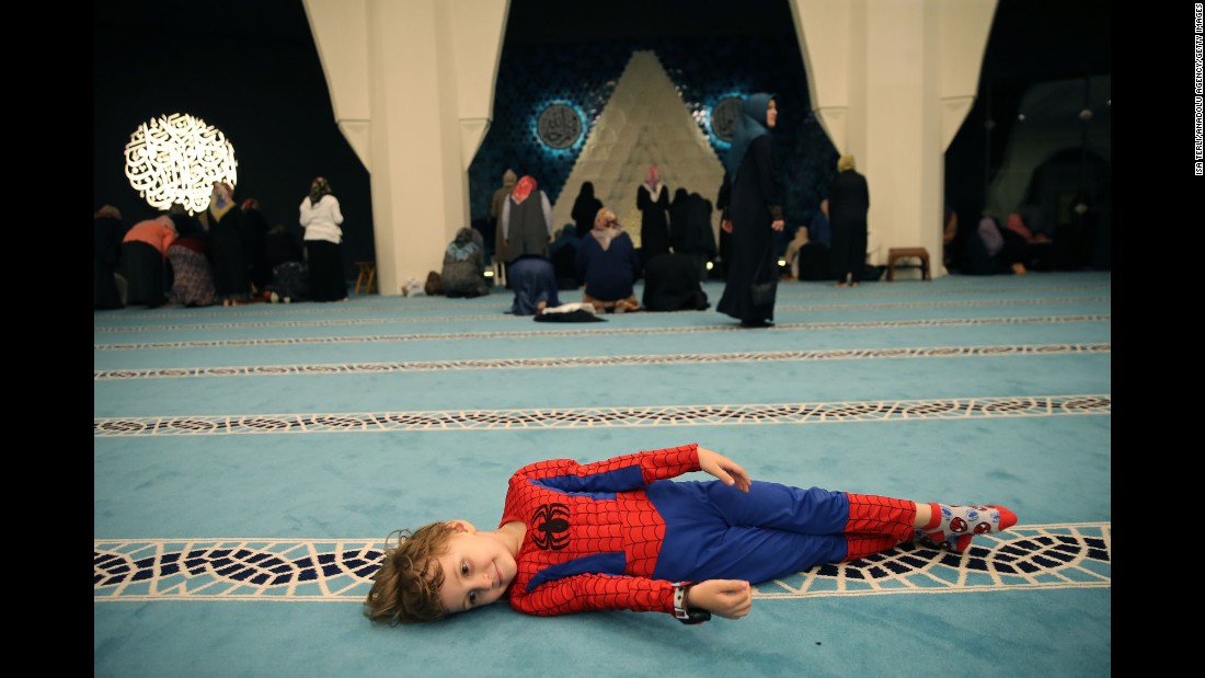 A child is dressed as Spider-Man as women pray at a mosque in Istanbul on Wednesday, June 14.