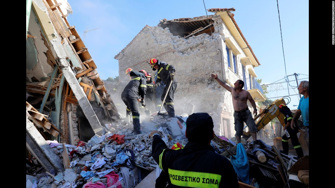 Rescuers search for victims at a collapsed building in Vrisa, Greece, after a strong earthquake shook the eastern Aegean Sea on Monday, June 12.