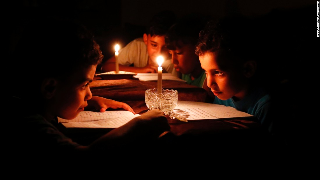 Because of electricity shortages, children in Gaza City read under candlelight on Tuesday, June 13.