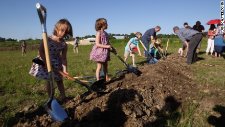 Children playfully shovel the dirt after a groundbreaking ceremony for the new Countryside Community Church earlier this month.