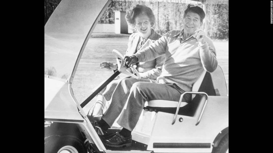 President Ronald Reagan takes British Prime Minister Margaret Thatcher for a spin in his golf cart, December 1984.