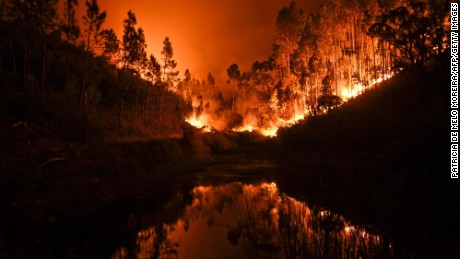 A wildfire is reflected in a stream at Penela, Coimbra, central Portugal, on June 18, 2017. Several hundred firefighters and 160 vehicles were dispatched late on June 17 to tackle the blaze, which broke out in the afternoon in the municipality of Pedrogao Grande before spreading fast across several fronts.