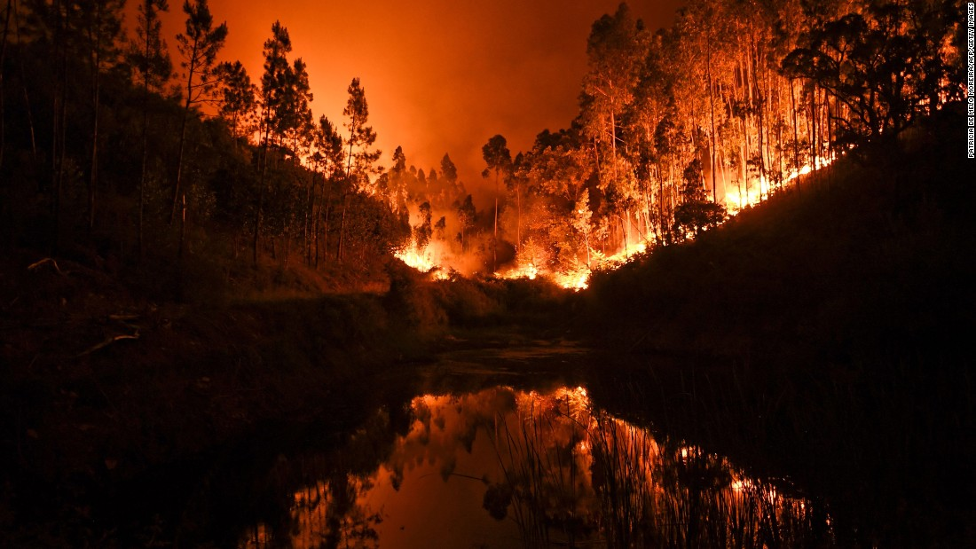A massive wildfire is reflected in a stream in central Portugal on Sunday, June 18, 2017. Several hundred firefighters fought the blaze, which broke out Saturday in the municipality of Pedrogao Grande.