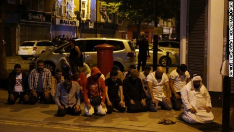 Muslims pray on a sidewalk in the Finsbury Park area of north London after a vehichle hit pedestrians, on June 19, 2017. 