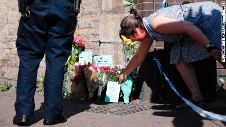 A woman lays flowers at a police cordon near the scene in Finsbury Park area of north London after a vehicle was driven into pedestrians, on June 19, 2017.