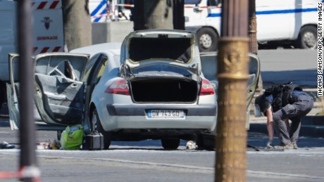 "A bomb disposal police officer (R)checks a car in a sealed off area on the Champs-Elysees avenue in Paris, on June 19, 2017 after a car crashed into a police van before bursting into flames, with the driver being armed, probe sources said.  A source close to the investigation said the driver was ""seriously injured"".  / AFP PHOTO / Thomas SAMSON        (Photo credit should read THOMAS SAMSON/AFP/Getty Images)"