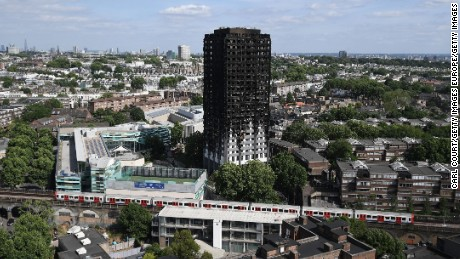 LONDON, ENGLAND - JUNE 16:  A tube train passes the remains of Grenfell Tower, seen from a neighbouring tower block on June 16, 2017 in London, England. 30 people have been confirmed dead and dozens still missing after the 24 storey residential Grenfell Tower block in Latimer Road was engulfed in flames in the early hours of June 14. Emergency services will spend a third day searching through the building for bodies. Police have said that some victims may never be identified.  (Photo by Carl Court/Getty Images)