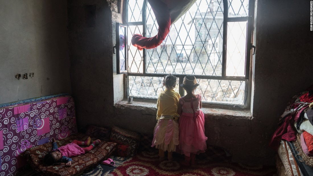 Children peer out of a window in a former government building in the suburbs of Ibb. The building was provided by local authorities to house 53 displaced families, but has no electricity or running water.