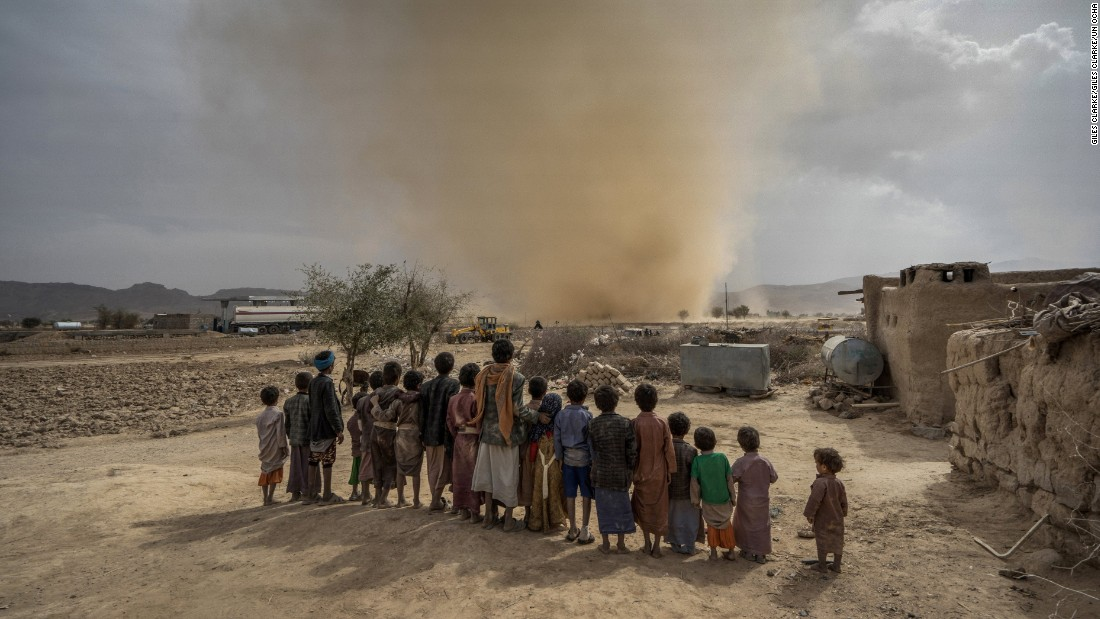 Children watch a mini tornado whip up sand as it travels across the desert near the town of Huth, 80km north of Sana'a. Aid agencies predict that by the end of the year, Yemen will be in a state of full-blown famine.
