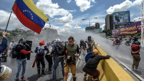 Opposition activists clash with riot police during a demonstration against the government of President Nicolas Maduro along the Francisco Fajardo highway in Caracas on June 19, 2017. Near-daily protests against President Nicolas Maduro began on April 1, with demonstrators demanding his removal and the holding of new elections. The demonstrations have often turned violent with 73 people killed and more than 1,000 injured so far, prosecutors say, and more than 3,000 arrested, according to the NGO Forum Penal.  / AFP PHOTO / Juan BARRETO        (Photo credit should read JUAN BARRETO/AFP/Getty Images)