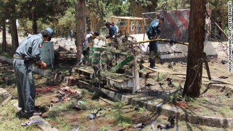 Afghan security forces inspect the site of a powerful car bomb Thursday in Lashkar Gah, Afghanistan.
