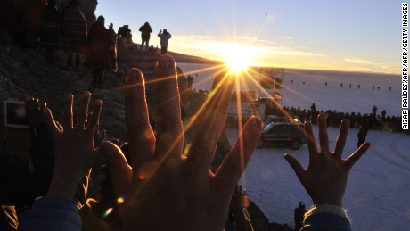 Aymara people raise their hands during a ritual at sunrise to celebrate the Aymara New Year on June 21, 2013 at the Uyuni salt flat in Bolivia. A crowd gathered to receive the first rays of Tata Inti (god Sun) during the celebration of the winter solstice that marks the beginning of the 5521st year in the Aymara calendar. AFP/PHOTO/Aizar RALDES        (Photo credit should read AIZAR RALDES/AFP/Getty Images)