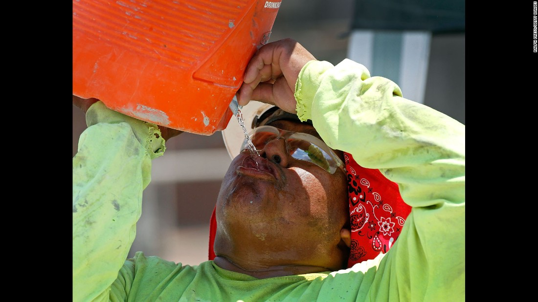 A construction worker drinks water at a job site in Phoenix on June 20.