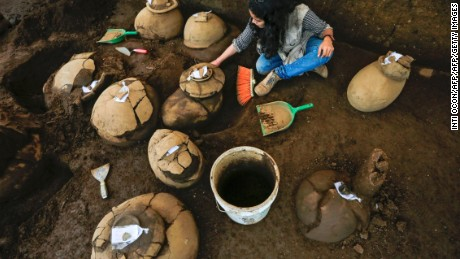 An employee of the Nicaraguan Institute of Culture (INC) works next to some 30 1,200-year-old pieces which were found in the surroundings of the construction site of the new National Baseball Stadium in Managua on June 20, 2017. / AFP PHOTO / INTI OCON        (Photo credit should read INTI OCON/AFP/Getty Images)