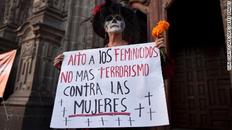 "A woman dressed as Catrina holds a sign reading ""Stop femicides. No more terrorism against women"" outside the Cathedral at the zocalo square in Mexico City on November 1, 2016.  Dozens of activists of feminist organizations dressed as Catrinas protested against femicides in Mexico City during All Saints Day. / AFP / YURI CORTEZ        (Photo credit should read YURI CORTEZ/AFP/Getty Images)"