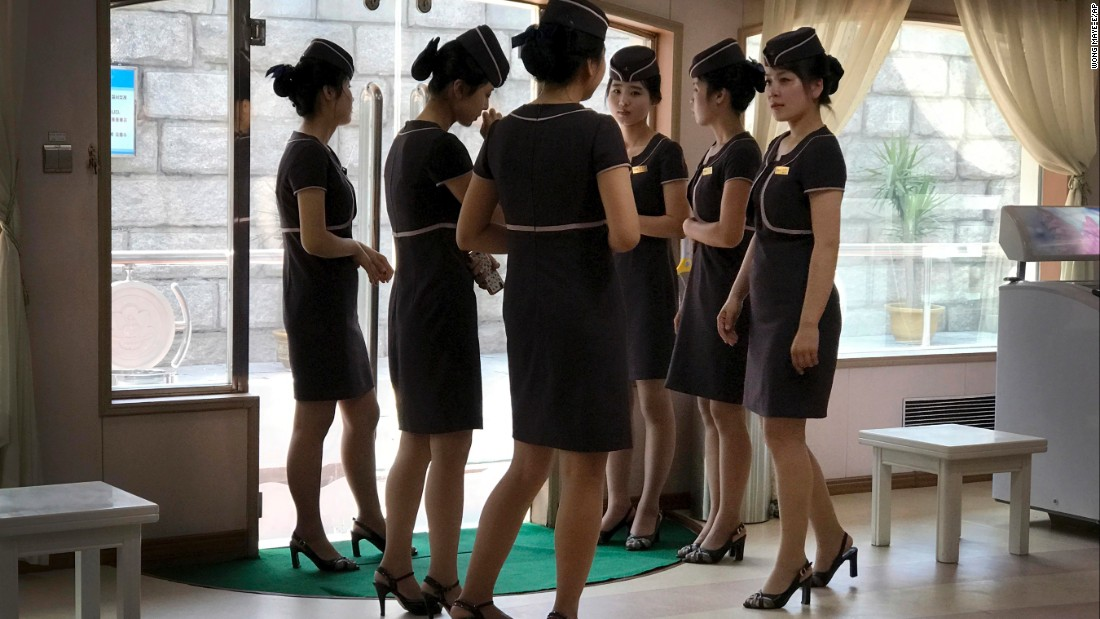 Staff of a boat restaurant on the Taedong River line up at the restaurant's entrance as they wait to greet customers in Pyongyang, North Korea, on Sunday, June 18.