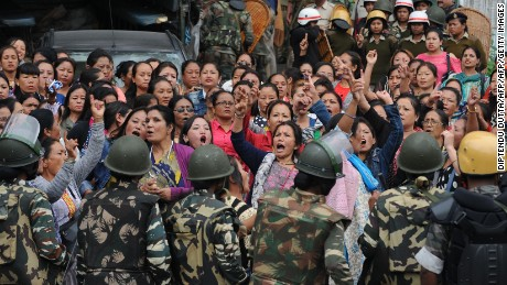Indian police personnel stop Gorkha Janmukti Morcha (GJM) supporters following a raid at the GJM office in Darjeeling on June 15, 2017.