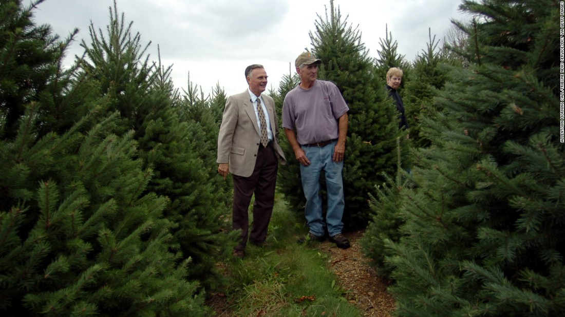 Gary Walters, chief usher of the White House, (left) talks with tree farm owner Francis Botek about picking out a Christmas tree for the Blue Room of the White House at Crystal Spring Tree Farm in Mahoning Township, Pennsylvania October 18, 2006. On the right is Margaret Botek.