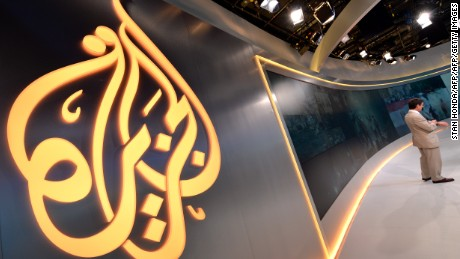 The Al Jazeera logo is seen in the new Al Jazeera America television broadcast studio on West 34th Street August 16, 2013 in New York as Paul Eedle (R), Deputy Launch Manager for Programing speaks to media during a tour. Al Jazeera America, which will launch on August 20, will have its headquarters in New York. AFP PHOTO/Stan HONDA        (Photo credit should read STAN HONDA/AFP/Getty Images)