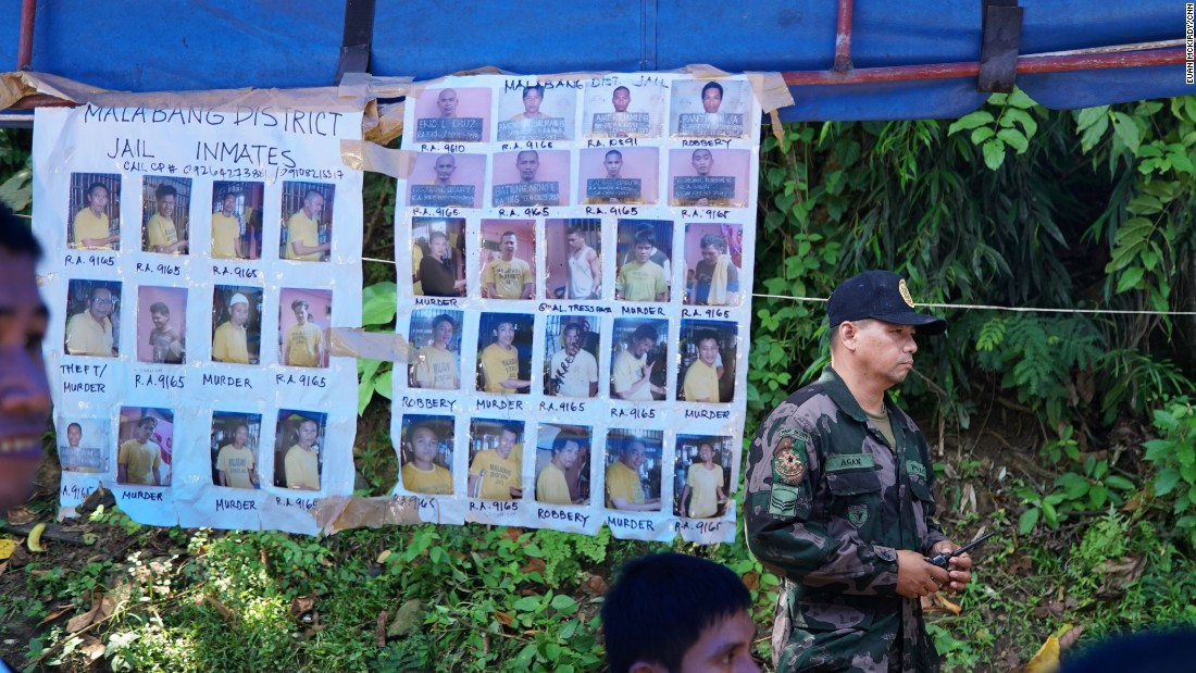 Posters featuring mugshots of suspected militants and escaped convicts hang under the awnings of a government checkpoint outside Iligan City in Mindanao.