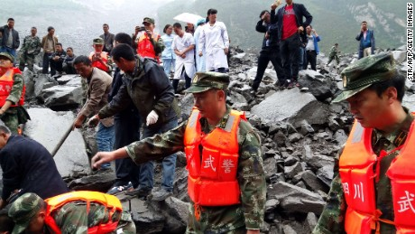 Chinese military police and rescue workers search the site of a landslide at the Xinmo village, in China's Sichuan province on, Saturday, June 24, 2017. Many people are feared buried after a landslide smashed through the village.