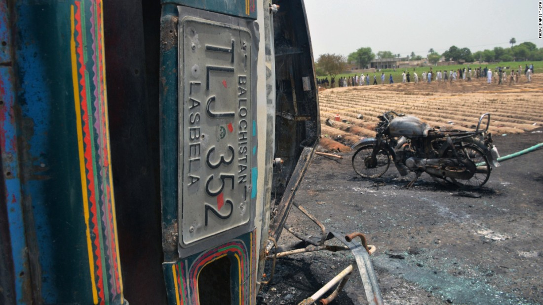 A burned motorcycle stands next to the wreckage of the tanker truck.