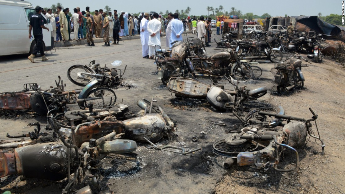 People gather behind burned motorcycles and vehicles at the scene of the explosion.