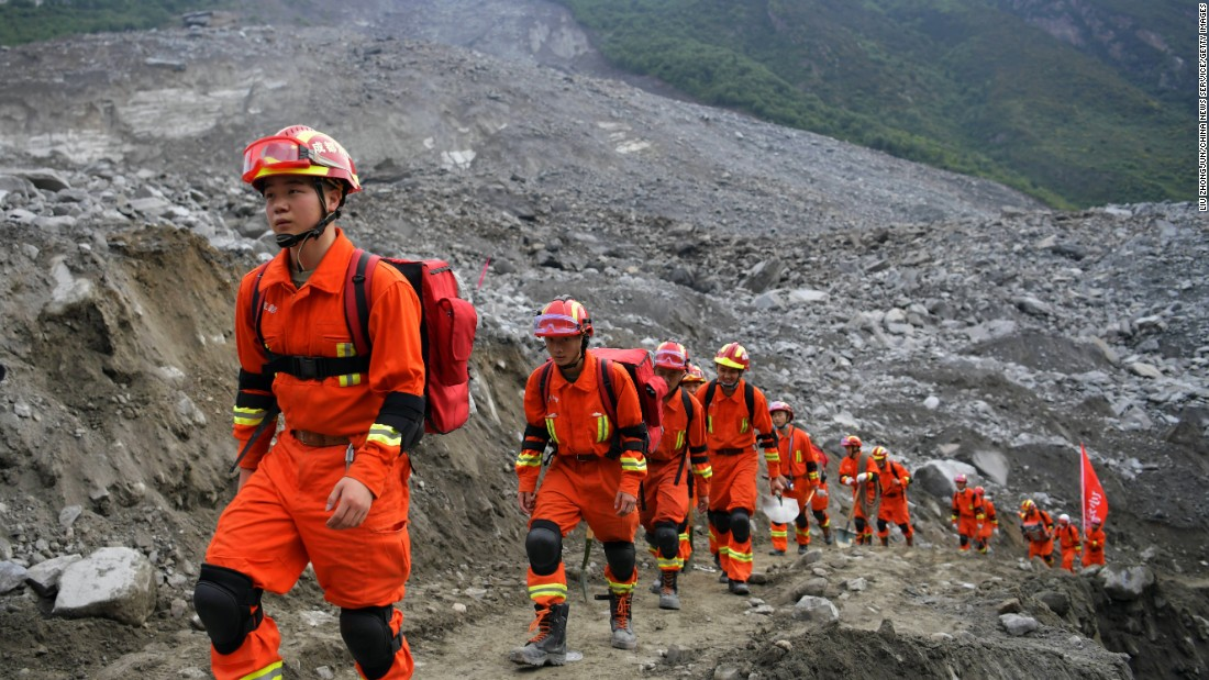 Rescue workers walk to the location where they will look for survivors of a massive landslide near Xinmo village in China's Sichuan Province on June 25. Heavy rains caused the side of a mountain to collapse onto the small village.