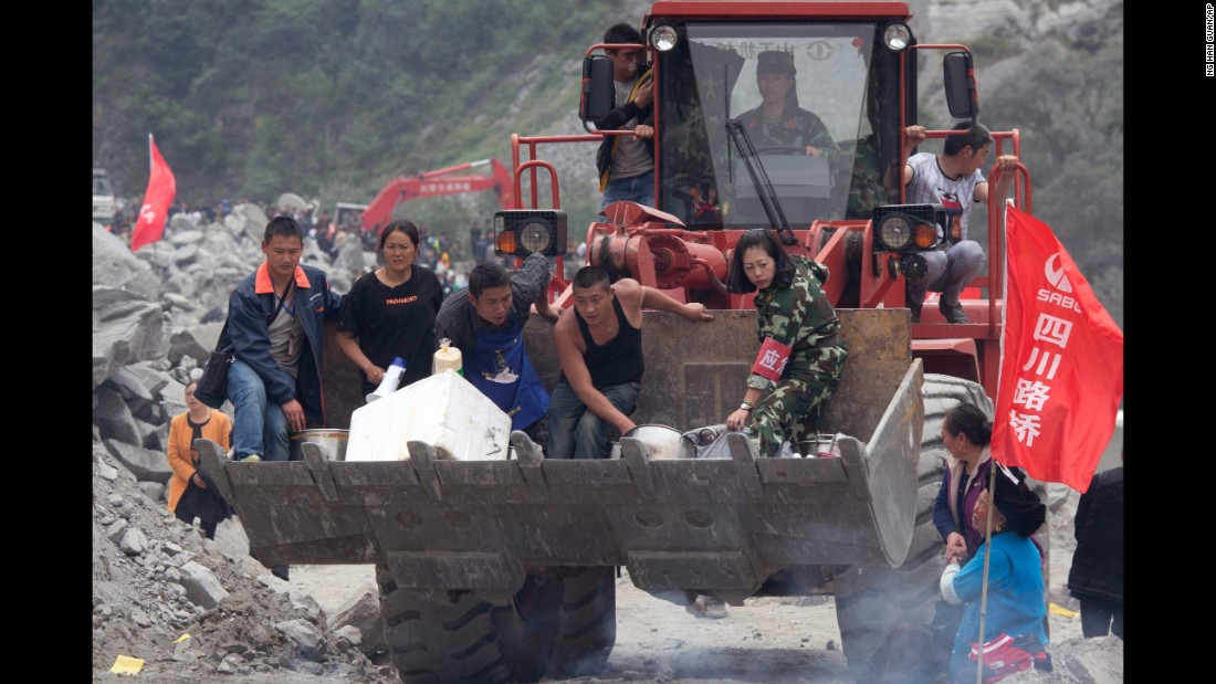 Volunteers deliver supplies to the site of a landslide on June 25.