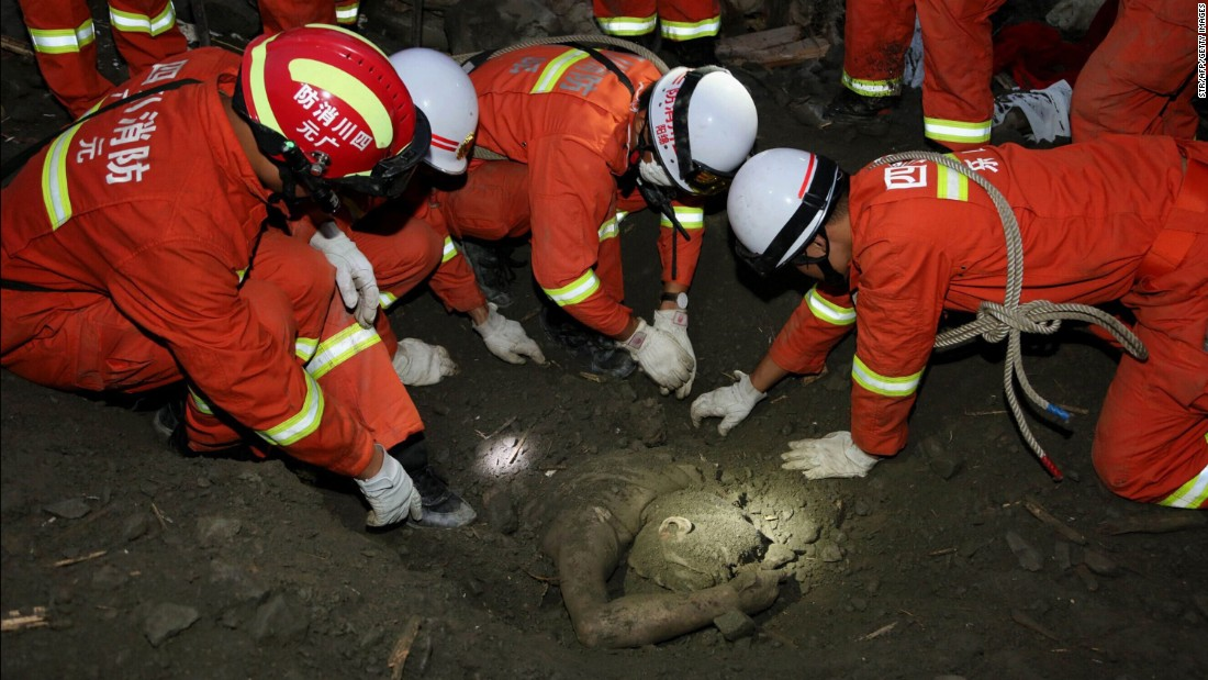 Rescue workers uncover the body of a victim June 24.