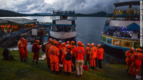 Rescue officials gather to take part in a search for survivors after the tourist boat Almirante sank in the Reservoir of Penol in Guatape municipality in Antioquia  on June 25, 2017.