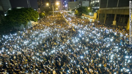 Protestors hold up their cellphones in a display of solidarity during a protest outside the headquarters of Legislative Council in Hong Kong on September 29, 2014.