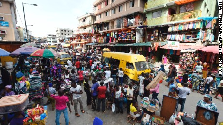 "Public transport minibus popularly called ""Danfo"" drive past roadside vendors along Balogun market in Lagos on May 10, 2017.  Fifty years on, Lagos is the world's 10th largest city with between 17 and 22 million people, although no-one seems to be counting. / AFP PHOTO / PIUS UTOMI EKPEI        (Photo credit should read PIUS UTOMI EKPEI/AFP/Getty Images)"