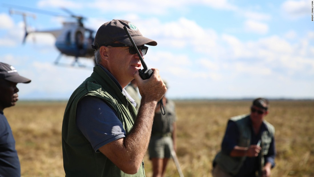 Wildlife vet Kester Vickery radios the helicopter team circling above. The air and ground teams work together to corral, dart and capture entire herds safely.