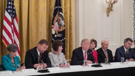 US President Donald Trump is flanked by US Senators Joni Ernst (L) of Iowa, Dean Heller (2nd L) of Nevada, Susan Collins (3rd L) of Maine, Lisa Murkowski (3rd R) of Alaska Orrin Hatch (2nd R) of Utah and Cory Gardner (R) of Colorado as Republican senators meet with Trump to discuss the healthcare bill at the White House in Washington, DC, on June 27, 2017. / AFP PHOTO / NICHOLAS KAMM        (Photo credit should read NICHOLAS KAMM/AFP/Getty Images)